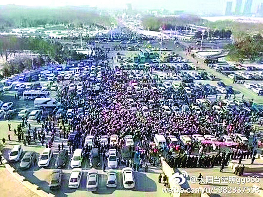 大圖:2月14日,黑龍江大慶上萬民眾齊聚市政府前廣場,抗議政府引進高污染項目忠旺鋁業。小圖:高舉抗議標語牌的大慶民眾。(網絡圖片)