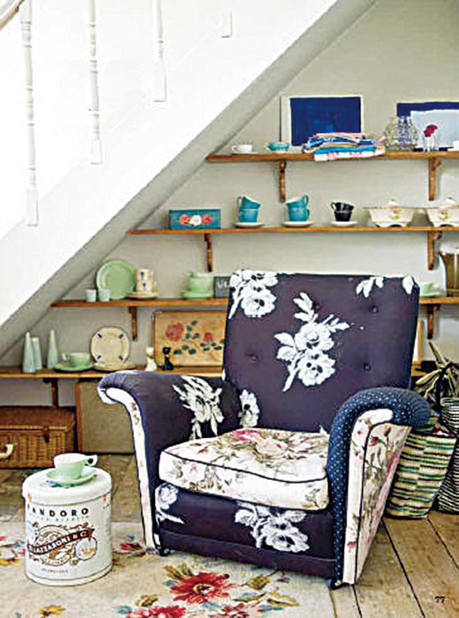 扶手椅套上搶眼的混合布料軟墊,可讓原本看來中性的空間添上手感風格。樓梯下的儲存空間另有一種風貌,使用開放式的架子展示瓷器外,前面還放了一張舒適的扶手椅。