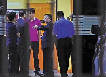 北韓大使館官員(中)在存放金正男遺體的吉隆坡中央醫院交涉。(AFP)