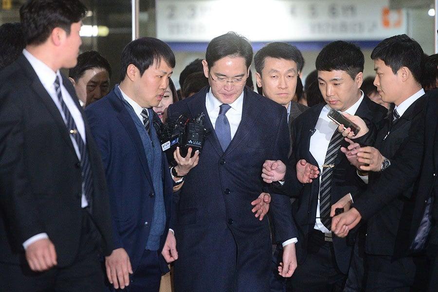 南韓法院以涉嫌對總統朴槿惠和其親信崔順實行賄對三星電子副會長李在鎔簽發了逮捕證。圖為16日李在鎔(左三)接受法院審查後走出法院的情景。(newsis)