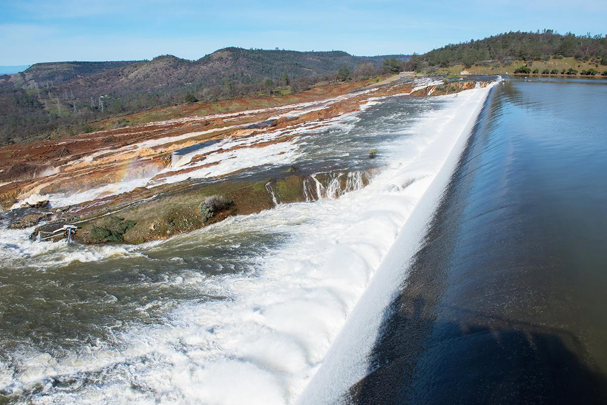 北加州暴雨導致奧羅維爾(Oroville Dam)水庫危機,引發近20萬人撤離。圖為2月12日,水庫水位繼續漫過擋水牆,直瀉而下沖入緊急洩洪道。(加州水資源部)