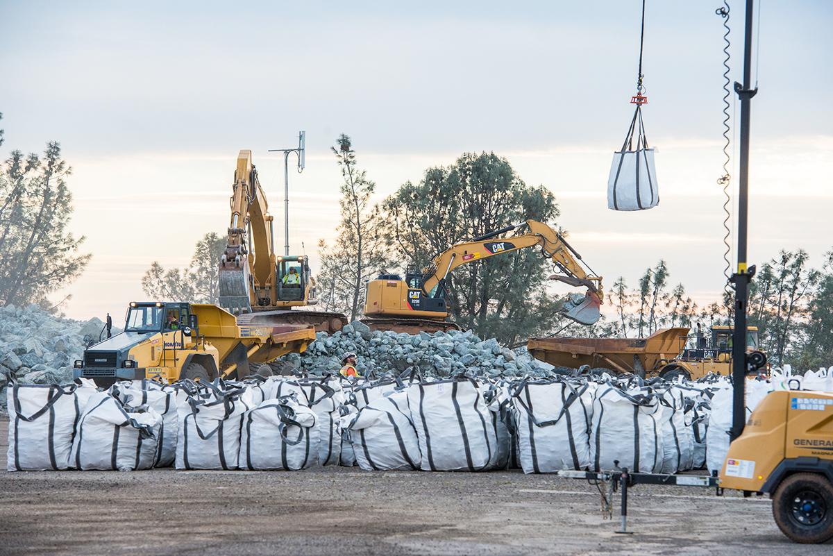 北加州暴雨導致奧羅維爾(Oroville Dam)水庫危機,引發近20萬人撤離。圖為2月13日,搶修人員用卡車和直升機運送開採的石塊,用於修補緊急洩洪道。大石塊用卡車運送,小一些的石塊裝入袋中用直升機運送。(加州水資源部)