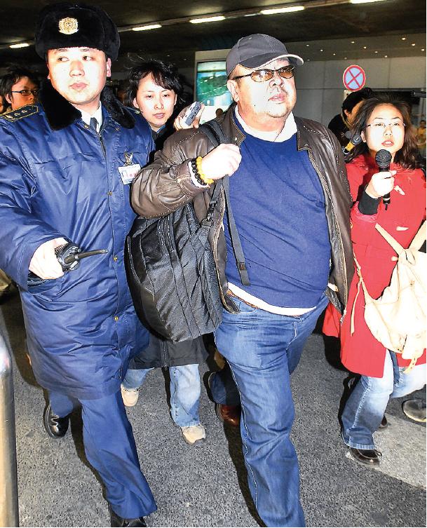 2007年2月,金正男在北京首都機場,其身邊除了記者外,還有穿制服的中方人員貼身護從。(AFP)
