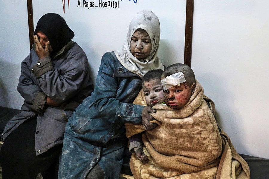 2017年2月20日,敘利亞政府軍攻擊首都大馬士革東北郊區民宅區,導致至少10人受傷。圖為一名婦女帶著兩名受傷兒童前往醫院就醫。(SARIA ABU ZAID/AFP/Getty Images)