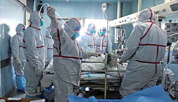 圖為2月12日湖北省武漢一家醫院,穿上全套保護衣的醫護人員治療H7N9患者。(Getty Images)