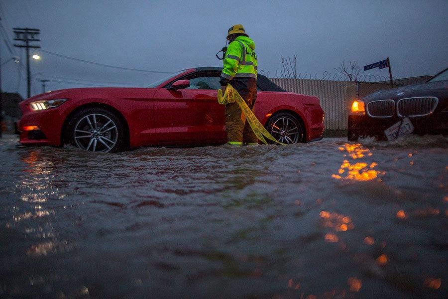 經歷多年的乾旱之後,加州大部份地區近期都遭受了強風暴雨的襲擊,不少車輛因為道路被淹而拋錨,等待緊急救援人員的幫助。(David McNew/Getty Images)