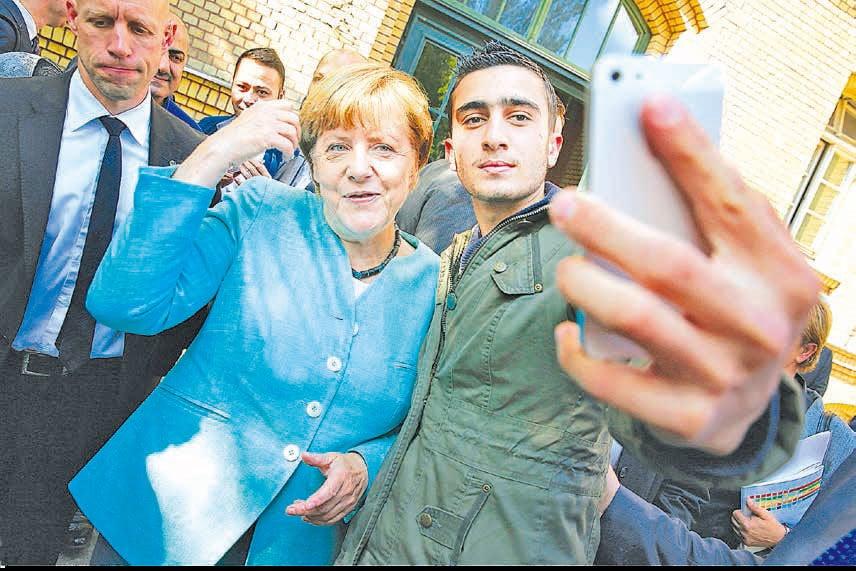 德國總理默克爾2015年9月10日在柏林參觀難民營住所,與難民合影。(Getty Images)