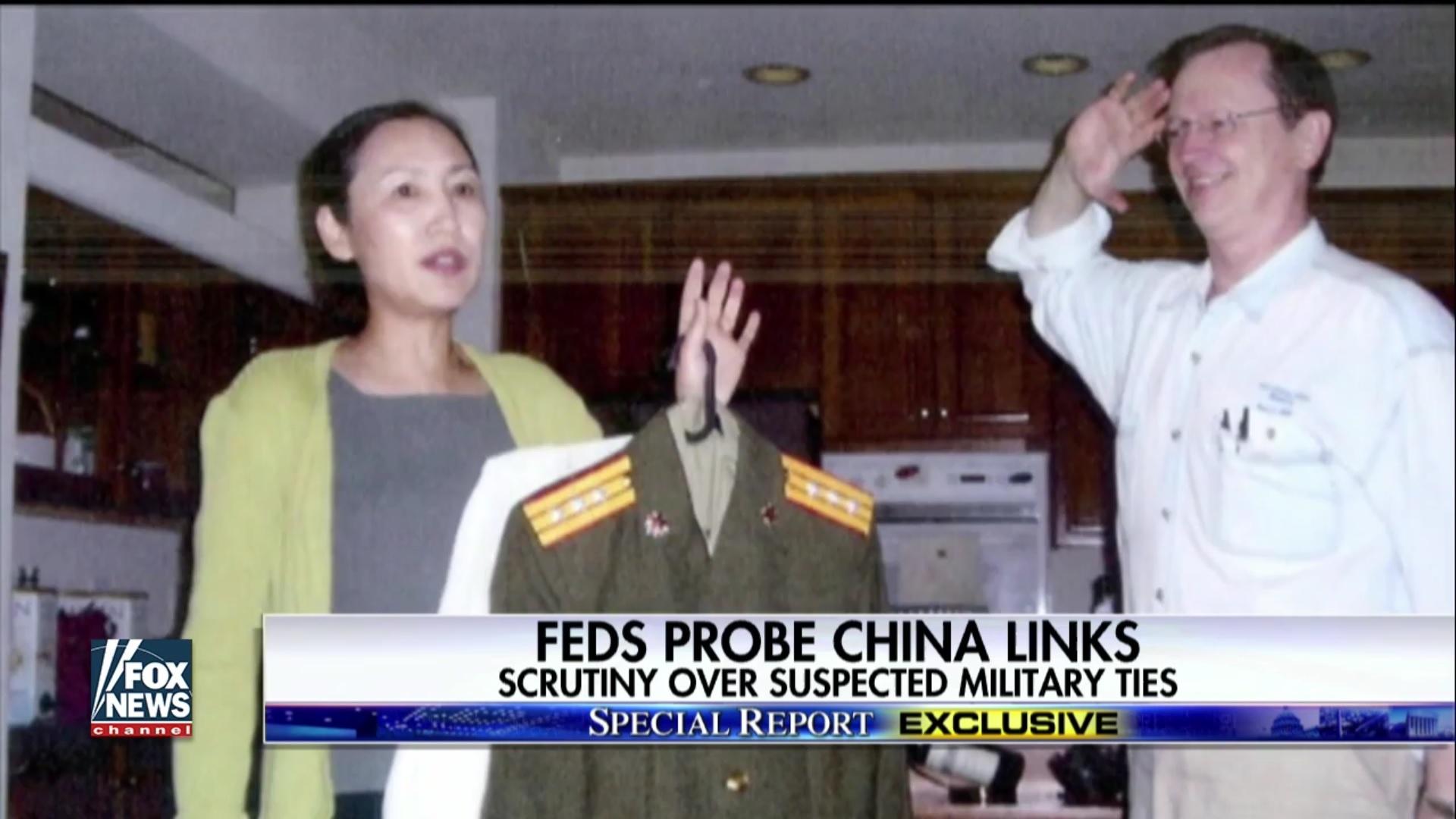 美國維珍尼亞州管理技術大學(UMT)創辦人陳燕平拿著中共軍裝,她的先生弗蘭姆向其行軍禮。(FOX新聞視像擷圖)