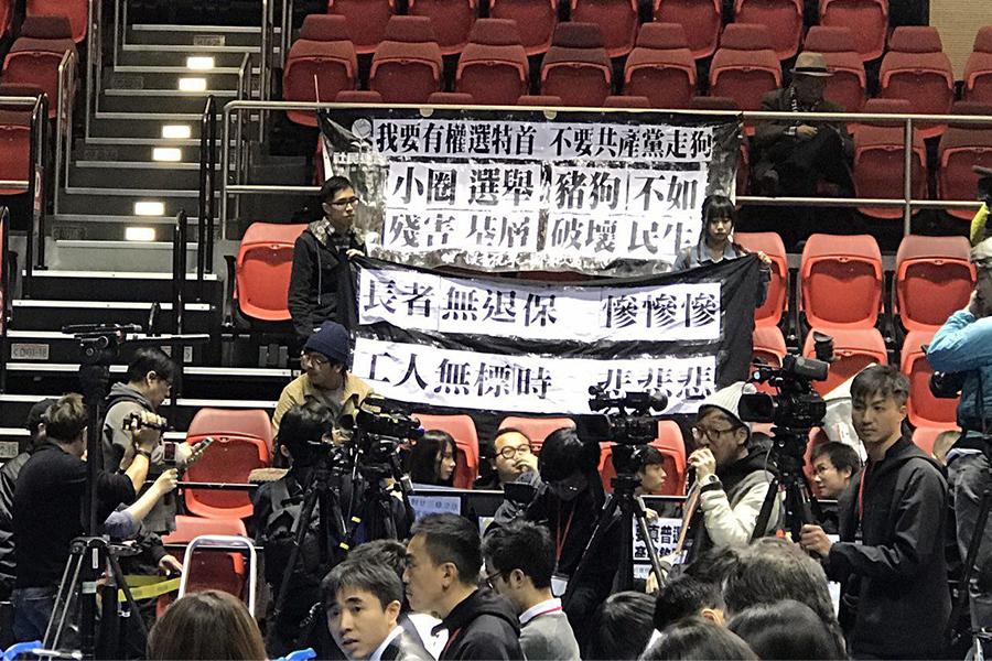 發佈會開始前,香港眾志、人民力量等多位成員成功闖入會場,舉起「反對廿三條立法」、「撤銷831」等標語,又高叫「林鄭可恥」、「打倒小圈子選舉」等口號。(林怡/大紀元)