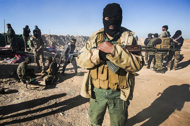 IS發佈影片,點名威脅要讓中國「血流成河」,武裝份子疑似新疆維族人。(AHMAD AL-RUBAYE/AFP/Getty Images)