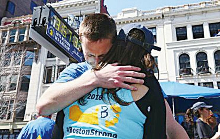 參賽者Downes以彎刀義肢跑完全程,與妻子感動相擁。