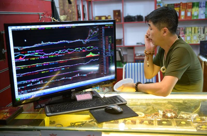 萬家文化被大陸證監會立案調查後,3月8日,萬家文化股價僅收於15.32元(人民幣,下同)。圖為中國大陸一股票市場。(PETER PARKS/AFP/Getty Images)