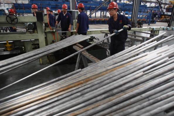 中國一家鋁製品工廠的工人在挪動鋁管。(Feng Li/Getty Images)