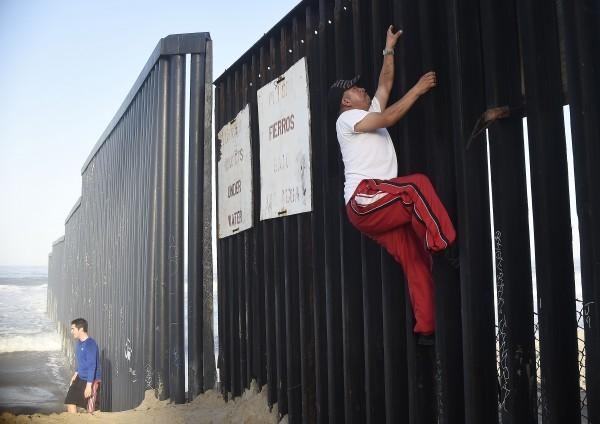 美國興建美墨圍牆的計劃已吸引600多家企業參與。圖為一名男子正在跨越美墨邊境。(RONALDO SCHEMIDT/AFP/Getty Images)