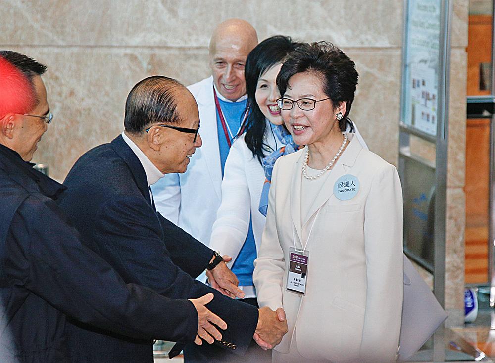 長江集團董事局主席李嘉誠(左二)和長子李澤鉅(左一)與林鄭握手。(李逸/大紀元)