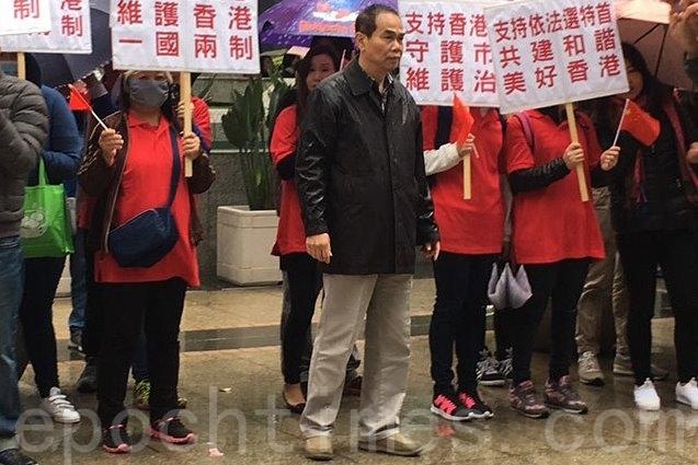 青關會頭目洪偉成在灣仔會展場外,指揮一批身穿紅衣、手持支持林鄭做特首標語的人。(大紀元)