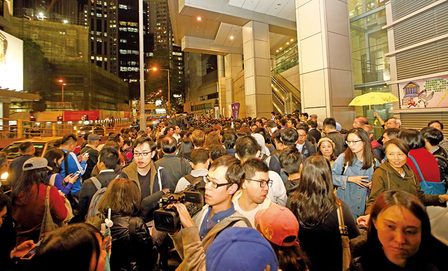 晚上約7時半,9人到灣仔警署接受預約拘捕,現場聚集了約200名支持者及本地及海外傳媒。(李逸/大紀元)