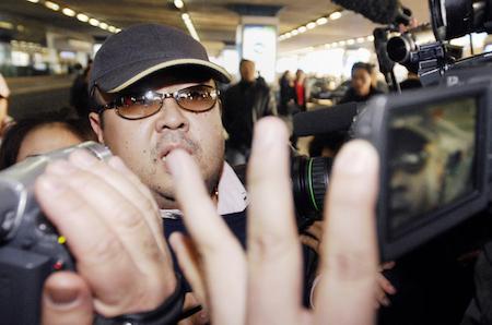 此照片拍攝於2007年2月11日,據信是金正男到達北京國際機場時,在一群記者中穿行。(JIJI PRESS/AFP/Getty Images)