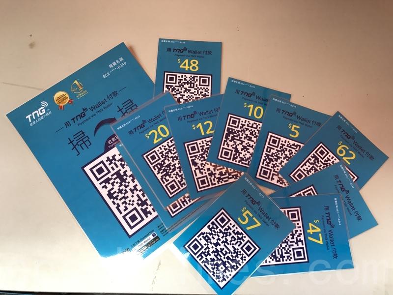 ,消費者在智能手機開設電子銀包戶口後,在報檔消費時掃瞄個別報販的QR Code,即可付款。(王文君/大紀元)