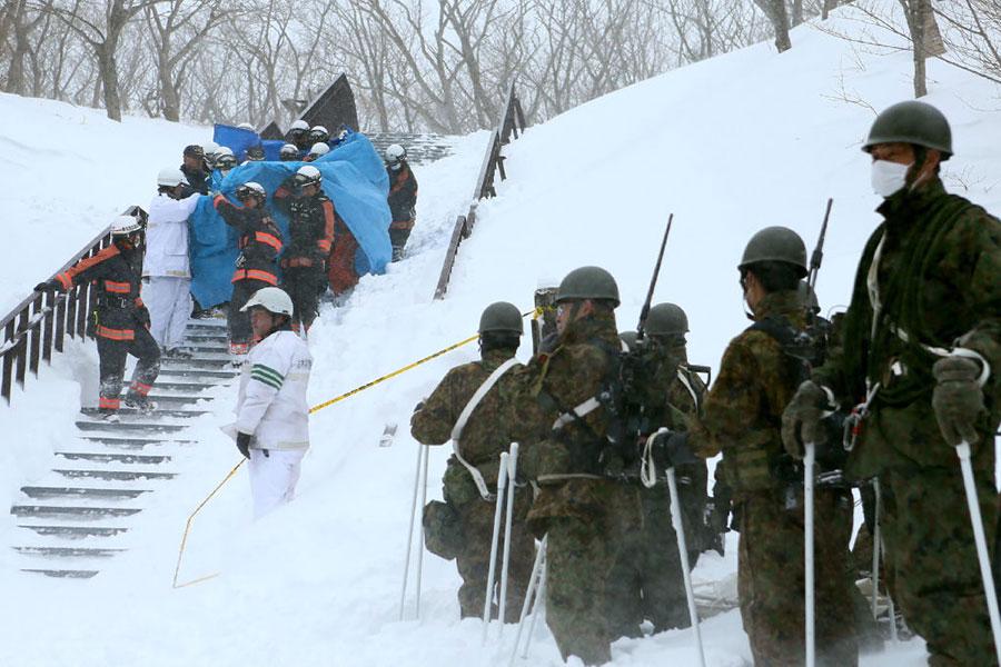 3月27日清晨,位於日本栃木縣那須町的一處滑雪場發生雪崩,7名高中生及1名領隊老師不幸遇難,40人受傷。圖為消防員和自衛隊參與救助。(Getty Images)