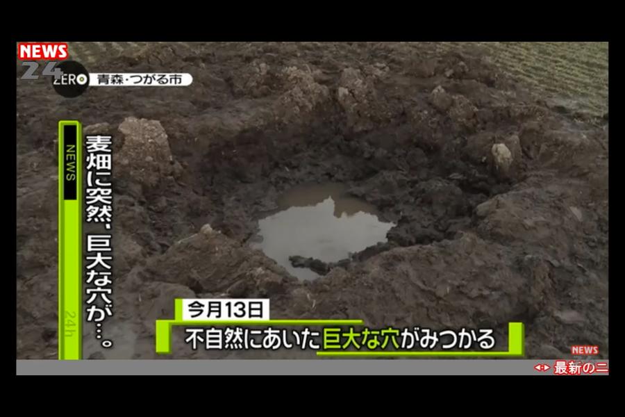 日本青森縣津輕市稻垣町一處麥田近日出現巨大坑洞,麥田的主人和不少專家都推測是天上掉落的東西砸出來的,認為可能是隕石造成的。(電視擷圖)