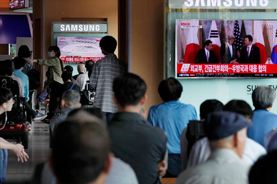 外媒報道,北韓或在本周五(3月31日)前完成核試的準備工作,並且可能在4月初習特會前進行第六次核試。圖為南韓民眾去年9月9日觀看北韓進行第五次核試報道。(Woohae Cho/Getty Images)