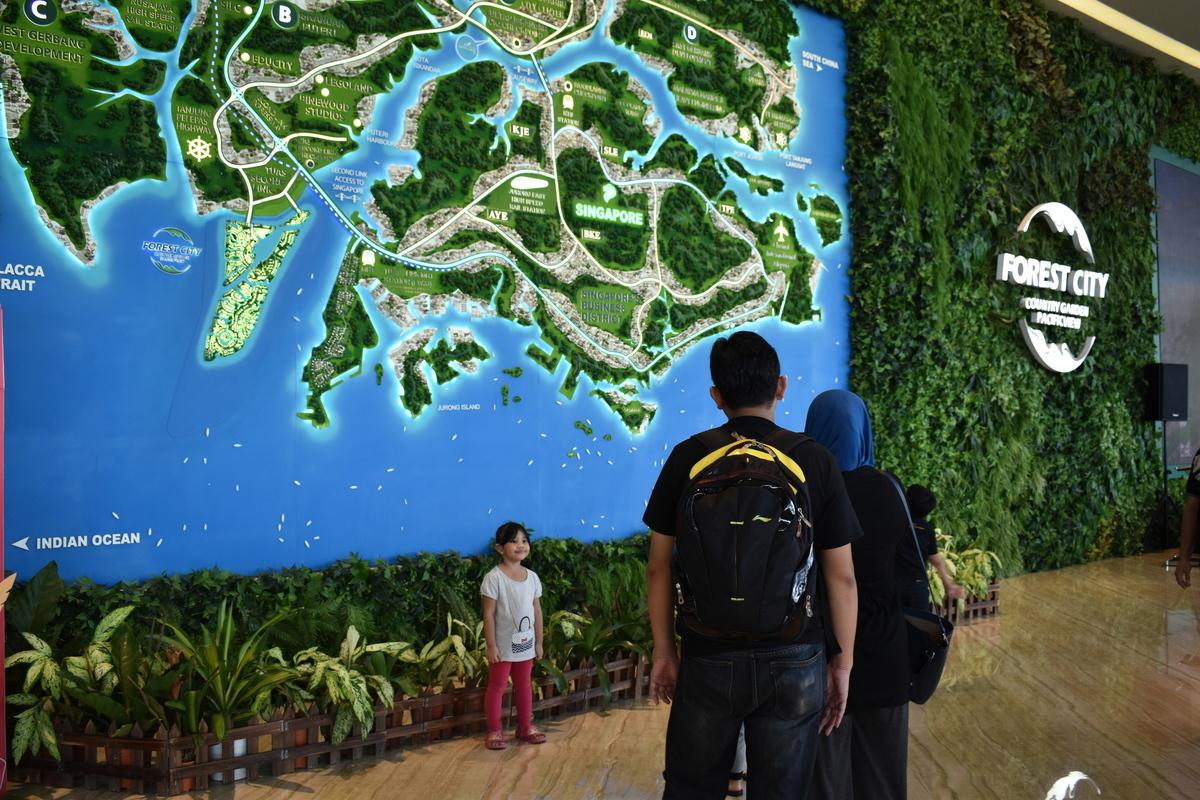 圖為內地地產商碧桂園在馬來西亞開發的名為「森林城市」(圖)的項目,曾經火熱的大陸購房的人潮在中國新年前後被觀光留影的當地人代替。圖為2017年1月30日正在該項目銷售大廳拍照的當地人。(容若/大紀元)