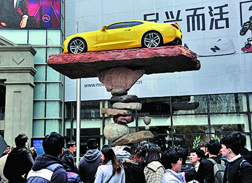 圖片新聞---近十塊石頭壘起 平衡頂起汽車