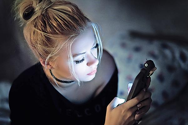 美國睡眠專家發現,常在使用智能手機或掌上平板電腦時睡著,屏幕產生的藍光會干擾大腦催眠的褪黑激素,進而影響睡眠時間和品質。圖為正在床上使用智能手機的女子。(Fotolia)