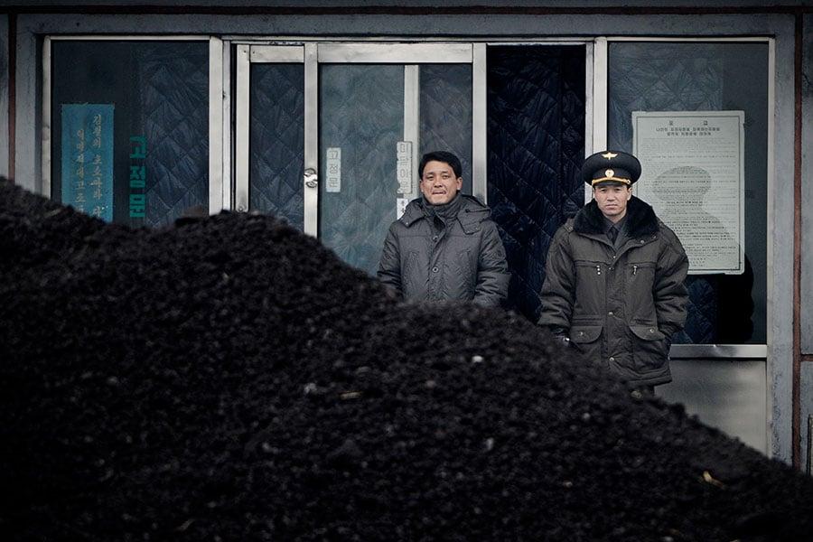 金正恩政權最大的收入來源,是每年向中共銷售數百萬噸媒炭,根據其官方統計,2015年和中共的煤炭交易金額佔其出口值的三分之一。圖為兩名北韓人站在煤炭前。(WANG ZHAO/AFP/Getty Images)