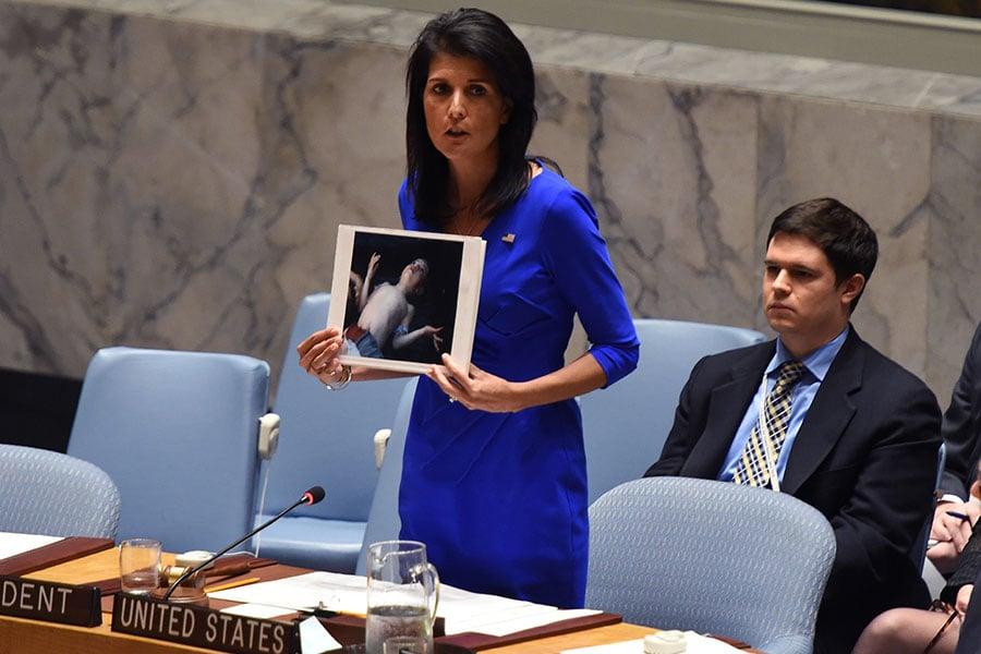 美國駐聯合國大使黑利(Nikki Haley)周三在聯合國安理會會議上,拿著4日遭毒氣屠殺的敘利亞遇難孩童照片,質問俄羅斯「在你關心之前,還要犠牲多少孩童?」。(TIMOTHY A. CLARY/AFP/Getty Images)