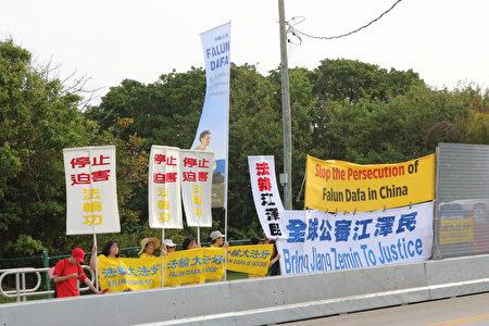 法輪功學員在馬阿拉哥莊園附近拉起橫幅,在習近平車隊通過時,呼籲「停止迫害法輪功」「法辦江澤民」,以及告訴他們「法輪大法好」。(澤霖/大紀元)