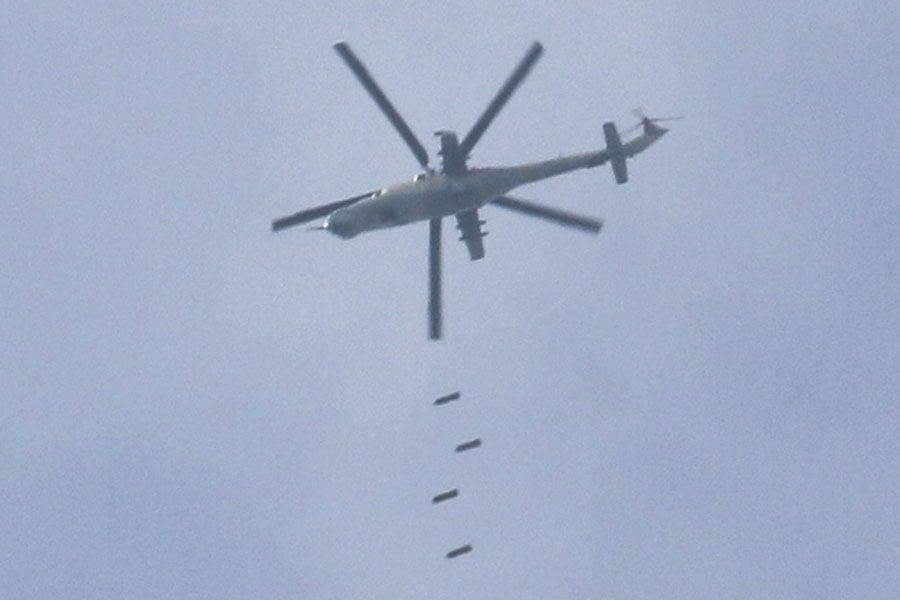 4月8日,一架敘利亞軍直升機在南部一座被反對派控制的城市,投放炸彈。(MOHAMAD ABAZEED/AFP/Getty Images)