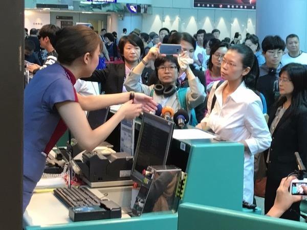 遭中共拘留的李明哲的太太李凈瑜(前左2)原訂4月10日搭機赴北京「救夫」,但台胞證卻遭註銷,李凈瑜上午到航空公司的櫃檯,要求了解為何台胞證會被註銷。(中央社)