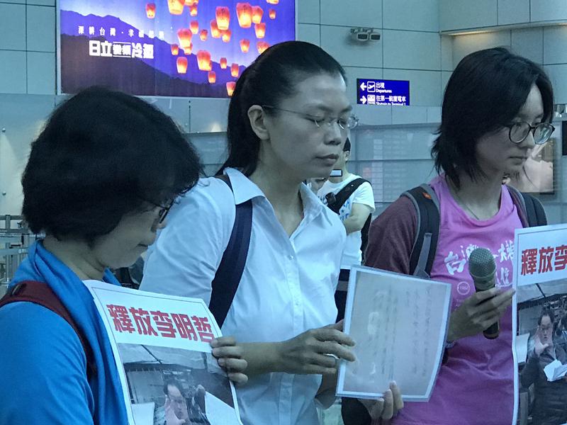 民進黨前黨工李明哲遭中共以「涉嫌危害國家安全」為由拘留,其妻李凈瑜(中)在機場向媒體記者出示對岸掮客寫給她的「保證書」。(中央社)