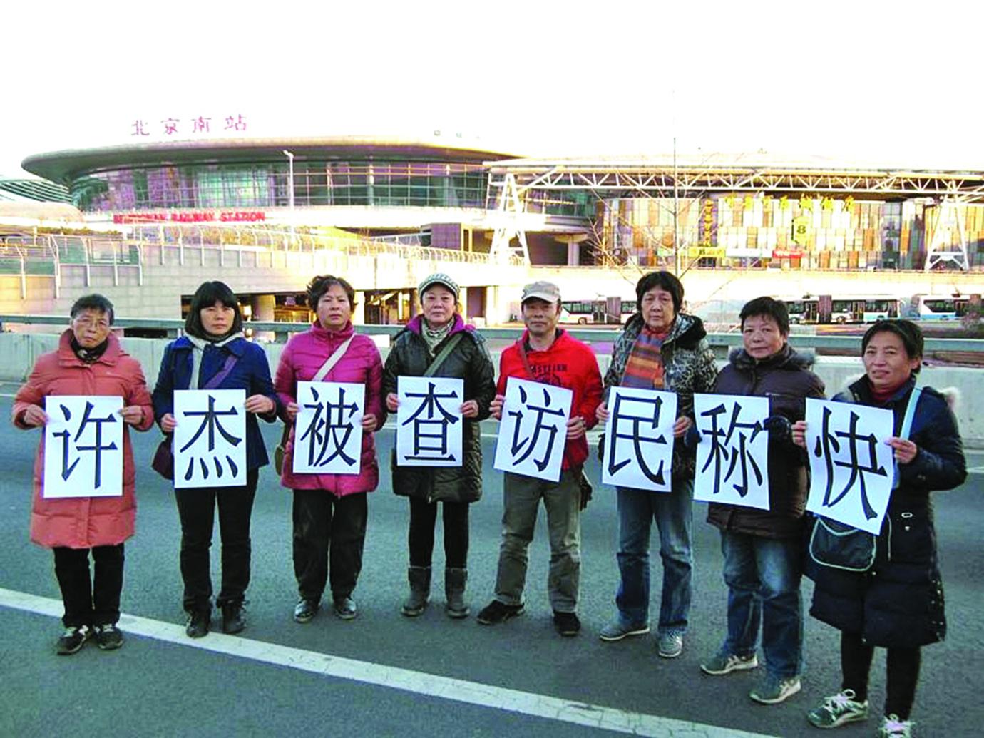 2013年11月28日,上海訪民得知中共信訪局副局長許傑落馬後,舉牌慶賀。(知情者提供)