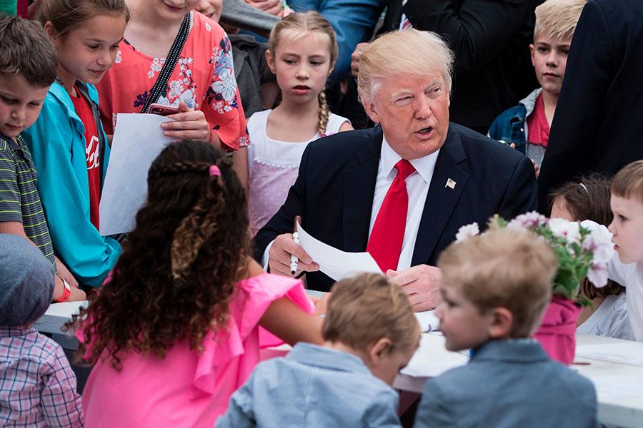 特朗普夫婦跟兒子巴倫一起觀看了滾彩蛋,並簽署了給軍隊的慰問卡。(BRENDAN SMIALOWSKI/AFP/Getty Images)