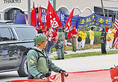 本月初習特會期間,中共領事館組織大量「歡迎人群」,有關人士企圖遮擋法輪功學員請願橫幅。(大紀元資料圖片)