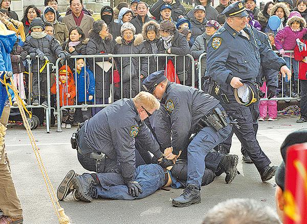 2011年2月12日在美國紐約法拉盛,一名華裔男子衝入法輪功遊行隊伍,拉扯橫幅並將其損毀,三名警察隨即制服並逮捕該人。(大紀元資料圖片)