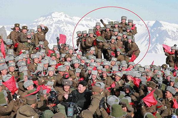中共官媒2015年4月報道,金正恩4月18日攀上白頭山的照片涉嫌造假。圖片中紅圈內的士兵登上了較高的地方,但腿後面的背景卻是白頭山天池的部份,人工合成的痕跡明顯。(網絡圖片)