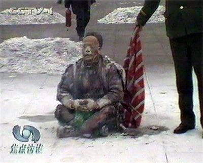 在天安門自焚偽案中,王進東自焚時,警察拿著所謂的「滅火毯」,卻垂在王進東的身後,垂在下面,是在做戲,不是在救「火」。(視像擷圖)