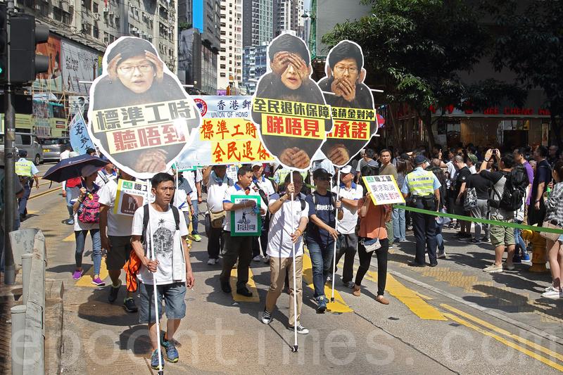 職工盟發起「勞動尊嚴、抗戰二十年」大遊行。有遊行人士手持3隻猴子道具,批評候任特首林鄭月娥漠視勞工訴求。(李逸/大紀元)