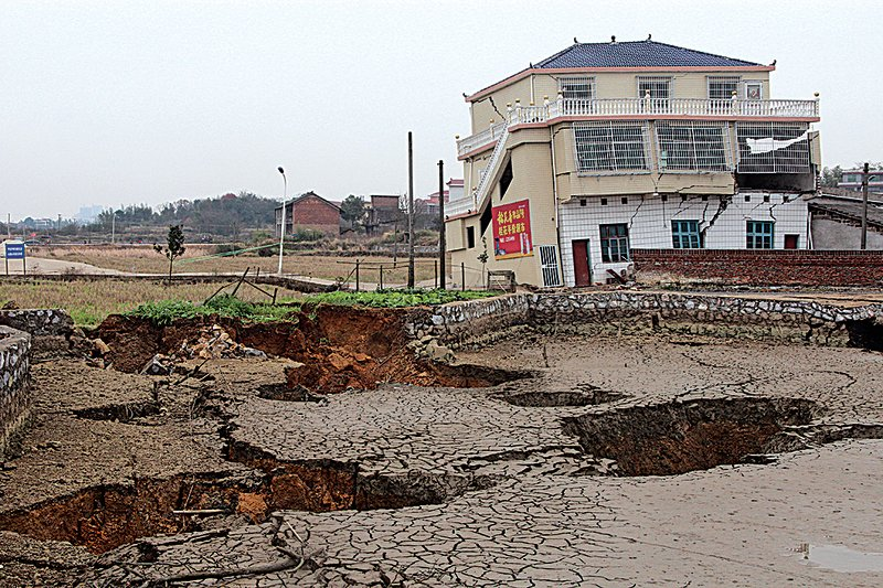 湖南邵東縣黃陂橋鄉多個村莊近日出現大量巨坑,因而造成房子斷裂歪斜。(大紀元資料室)