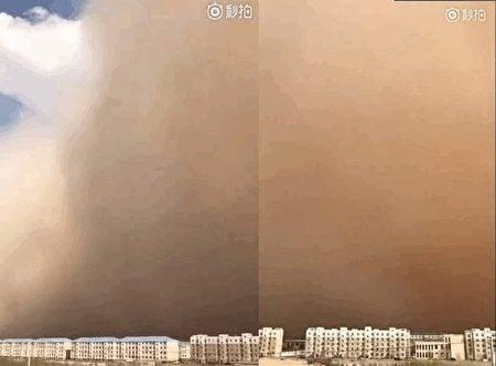 內蒙古二連浩特市出現沙塵暴天氣,百米高的沙牆被大風席捲而來,天昏地暗,能見度低於500米。(視像擷圖)