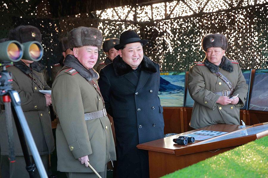 圖為金正恩(中)視察北韓人民軍大聯合部隊實戰訓練,受到當時的北韓人民武力部長朴永植、北韓人民軍總參謀長李明洙(前排左)等迎接。(AFP PHOTO / KCNA VIA KNS)