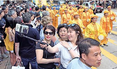 遊行途經購物熱點尖沙咀廣東道時,大陸遊客雀躍地與遊行隊伍合照。