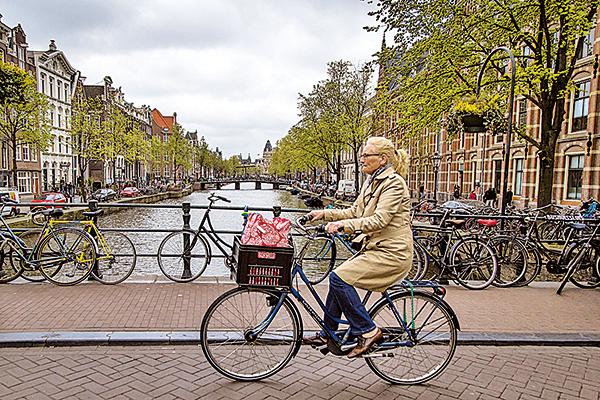 在歐洲,騎單車和開車享有同樣的權利,也因為騎車是「人包鐵」,所以往往可以享有更多的優惠與禮遇。圖為荷蘭街景。(Getty Images)
