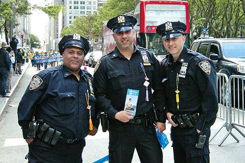 維持遊行秩序的警察手持法輪功單張,胸前佩戴學員送的小蓮花,警員Anthony(左)說每個人都應修煉法輪大法。(明慧網)