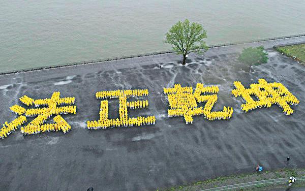 兩千名法輪功學員冒雨在總督島排出壯觀的「法正乾坤」四個大字。(曹景哲/大紀元)