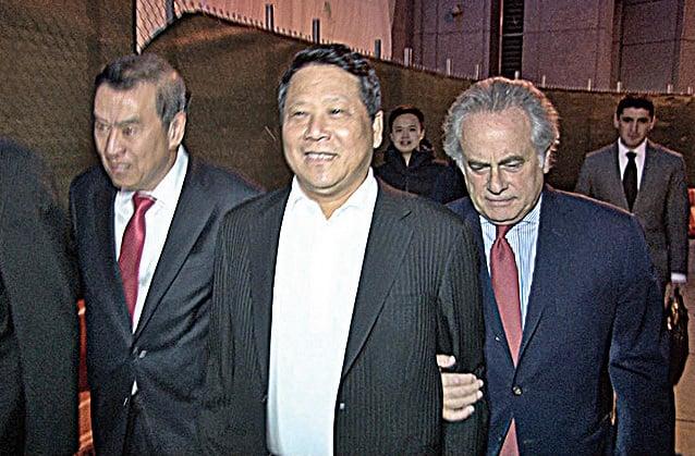 2015年10月,涉賄賂前聯大主席阿什的澳門政協委員吳立勝(中)在兩名代表律師攙扶下走出法庭。(大紀元資料圖片)